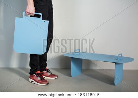 Man in black jeans stands and red sneakers with a metal cyan panel in his hand on the gray wall background. Next to him there is a small metallic blue stand. Closeup photo. Indoors. Horizontal.