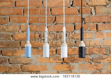 Four multicolored lamps with light wooden parts are hanging on the cables on the brick wall background. They are cyan, gray, white and black colored. Closeup. Horizontal.