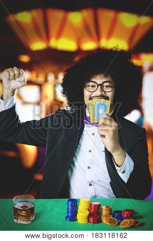 Afro man celebrating his winning while holding poker card and a glass of beer on the table