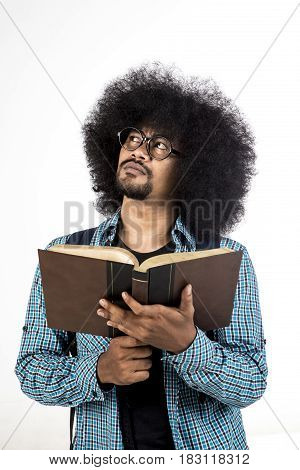 Afro man thinking solution while holding a book in his hand isolated on white background