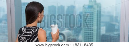 Woman drinking coffee looking through window at view of city skyline at home, cafe or office building. Pensive businesswoman relaxing at work in Shanghai, China.