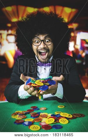 Cheerful Afro person with curly hair winning a gambling in the casino and holding many chip on his hands