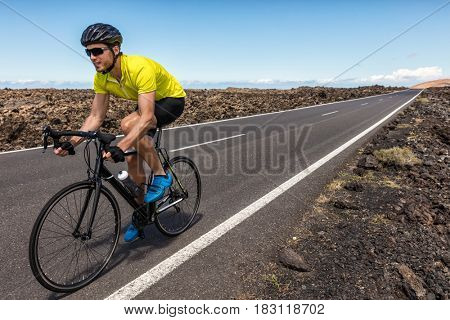 Professional cyclist riding racing bike in race competition on open road. Sports athlete man biking with high intensity on highway during summer cardio workout training for triathlon.