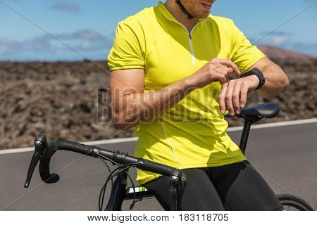 Biking Athlete cyclist using an activity tracker gps smartwatch during biking workout training race. Road bike sports man using his watch app for fitness tracking. Healthy lifestyle.