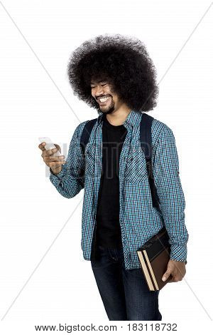 Afro college student looking his smartphone while holding book and standing in studio isolated on white background