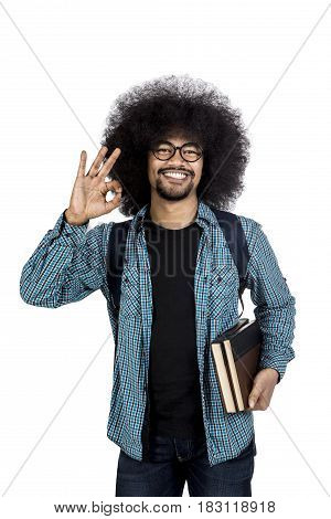 Afro male student showing ok gesture while holding book and standing in studio isolated on white background