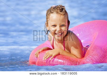 Happy smiling girl in an inflatable ring swimming in the Baltic Sea.