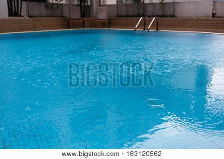 Swimming pool with clear blue water with ladder and deck chairs