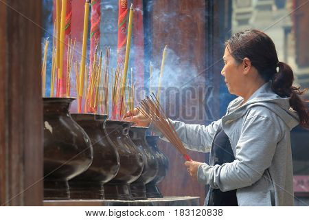 HO CHI MINH CITY VIETNAM - NOVEMBER 27, 2016: Unidentified woman pray at Thien Hau temple. Thien Hau temple is a Chinese style temple of the Chinese sea goddess Mazu in Chinatown.