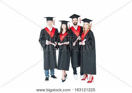 Full length front view of happy students in graduation caps holding diplomas on white