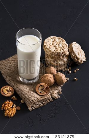 Organic food. Glass of milk or yoghurt with nuts and diet crispbreads, still life on black background