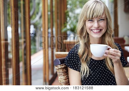 Portrait of young woman taking a coffee break