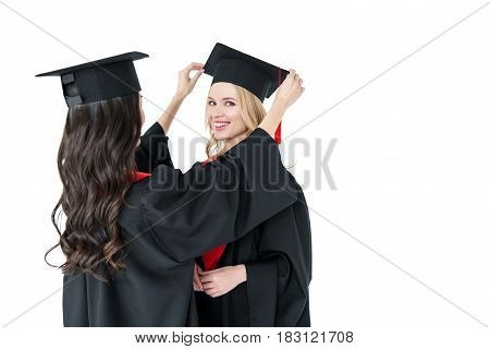 Two Young Happy Women In Mortarboards Standing Together On White Background