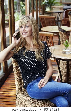 Young blond woman taking call in cafe