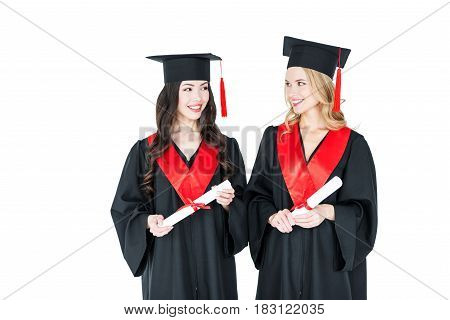 Two Beautiful Young Students In Academic Caps Holding Diplomas And Smiling Each Other