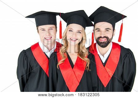 Happy Students In Mortarboards And Mantles Smiling At Camera