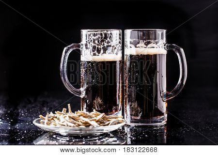 Photo of beer mugs with anchovies on empty background