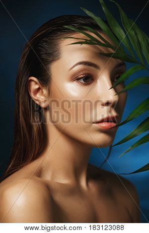 Fashion concept. Closeup of amazing woman covering face behind green leafs on dark blue background.