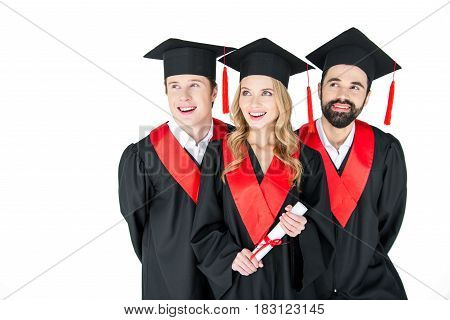 Happy Students In Mortarboards And Graduation Gowns Looking Away On White