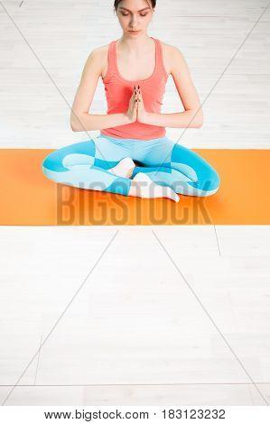 Girl in lotus pose on orange rug in gym