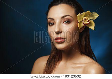 Fresh makeup look. Natural finish. Naked woman with slicked back hair, looking straight at camera.