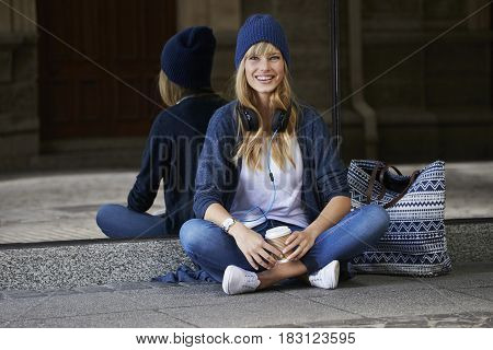 Young woman in city chic looking at camera