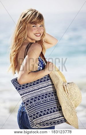 Beautiful blond beach girl with bag portrait