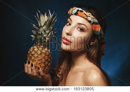 Side shot. Portrait. of shirtless woman with striped durag, holding exotic fruit and looking straight.
