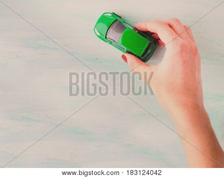 Toy child car in woman's hand. Top view on bright wooden textured background. Purchase insurance bank loan travel where to go trip journey concept. Toned
