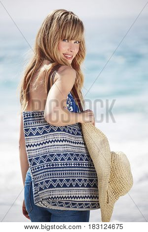 Gorgeous beach girl with bag and hat portrait