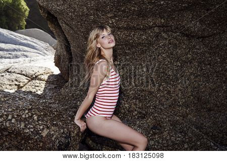 Swimsuit beauty sitting on rocks at beach