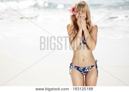 Giggling young woman at beach in bikini