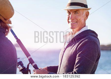 Senior man fishing with his grandson to fish at sea