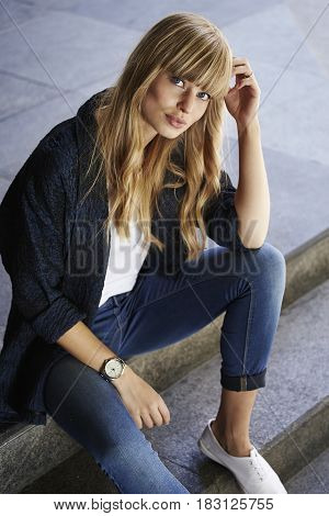 Blonde confident beautiful woman sitting on steps