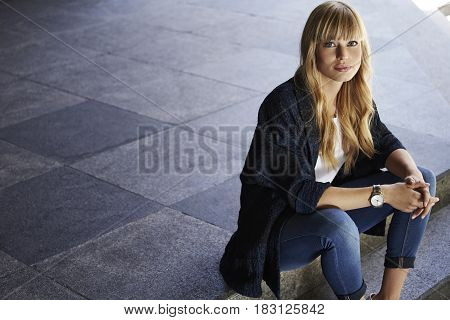 Blond beautiful relaxed girl sitting on steps