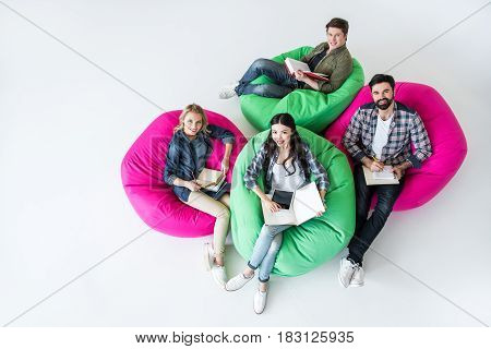 overhead view of students sitting on beanbag chairs and studying in studio on white