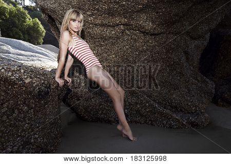 Posing swimsuit babe on rocks at beach
