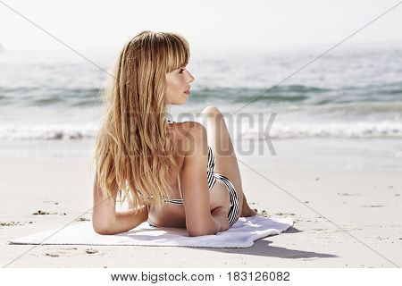 Blonde babe relaxing on beach on vacation