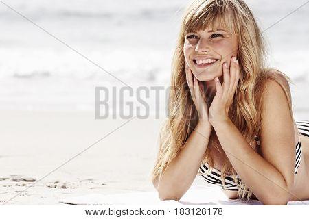 Happy sunbathing blonde babe on beach smiling