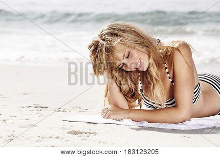 Beautiful babe sunbathing on beach with ocean background
