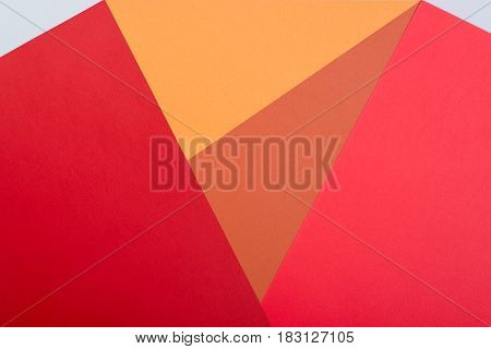 Color papers geometry flat composition background with pinkred orange and grey tones.