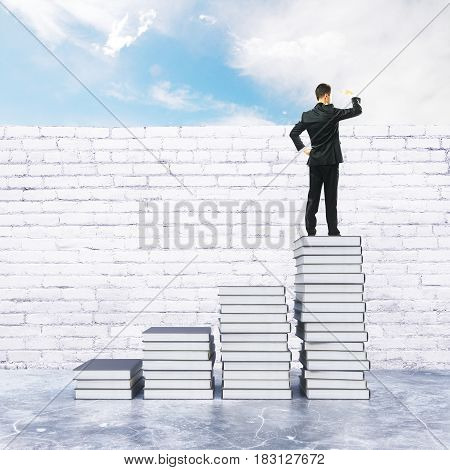 Young businessman on top of creative book ladder looking into the distance. Research concept. 3D Rendering