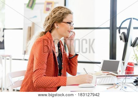 Young woman holding mobile phone in office