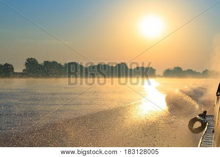 Waves from speed transportation ship in the morning sunrise and fog on Danube river channel Sulina
