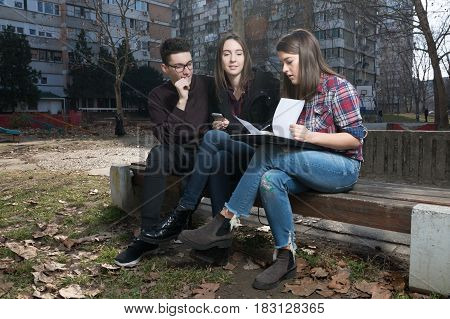 Three high school teenager students with laptop in the playground