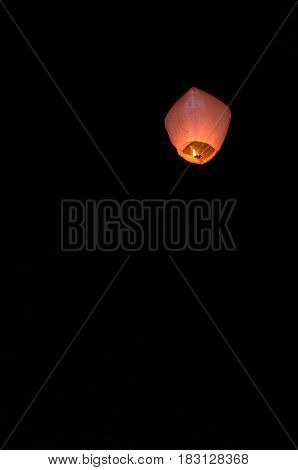 Flying light lanterns in the night sky.