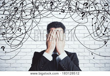 Stressed young businessman with scribble and question marks on white brick background. Confusion concept