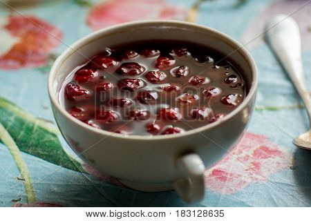 Cup with cherry compote on a rustic table