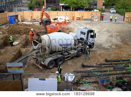 Bracknell, England - April 24, 2017: Overhead view of a cement mixer and construction workers laying the foundations of a new retail property development in Bracknell, England