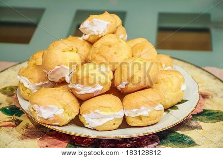 Closeup of fresh baked cream puffs filled with white whipped cream on a plate